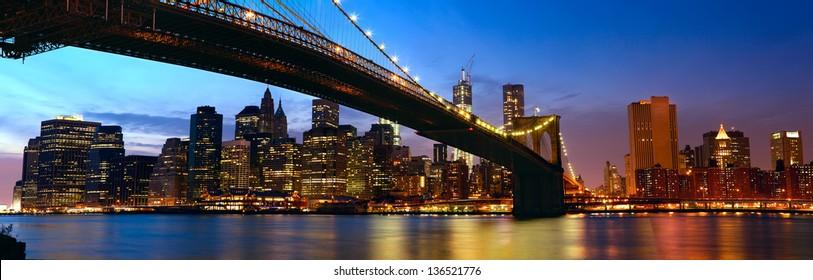 Lower Manhattan skyline panorama with Brooklyn Bridge at sunset in New York City