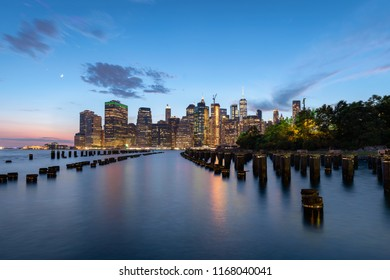 Lower Manhattan Skyline view after sunset from Brooklyn Bridge Park. The East River and pier 1 pylons are visible in the foreground.