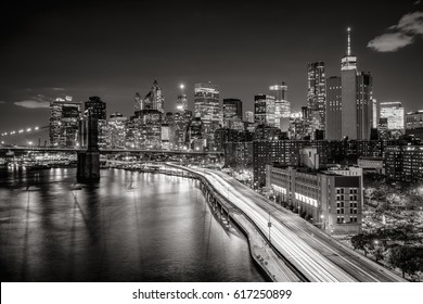 Lower Manhattan skyscrapers and Financial District. The Black & White elevated night view includes the West tower of the Brooklyn Bridge, East River and traffic light trails on the FDR Drive. New York