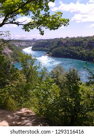 The lower Niagara gorge rapids in Niagara Falls Ontario seen through an opening in the cliff forest.