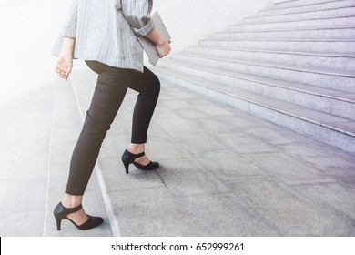 Lower part of Business Working Woman in high heel shoes walking up stair at city outdoor, side view, Success and Motivation of Modern Female concept