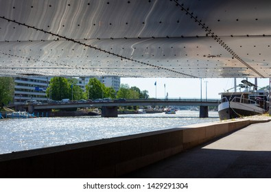 The lower part of the low bridge with metal plates and rivets passes through the Auraioki River and above the embankment and overlooks the embankment of the city of Turko Abo in Finland