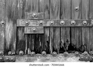 Lower part of an old heavy wooden door in ancient house. B&W