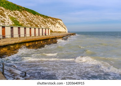 The lower promenade and beach huts along the white chalk cliffs at high tide at Dumpton Gap, Broadstairs, in Thanet, Kent, UK