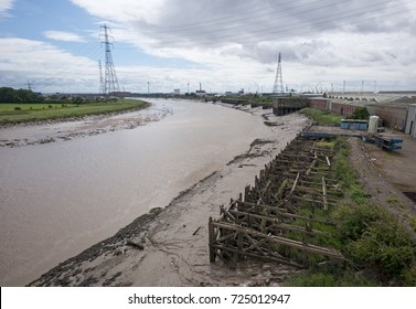 Lower reaches of River Usk from western side of Newport Transporter Bridge with disused and derelict wooden wharves in foreground. Newport, Wales, UK