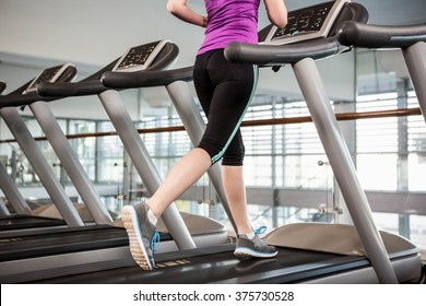 Lower section of fit woman on treadmill at the gym