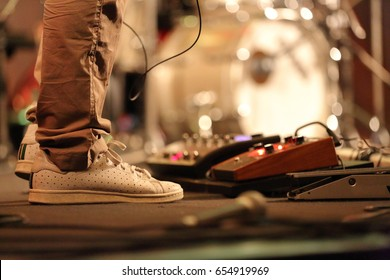 lower section leg and feet of electric guitar playing musician wearing sneakers