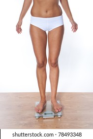 Lower section legs of a young woman measuring her weight while standing on weighing machine
