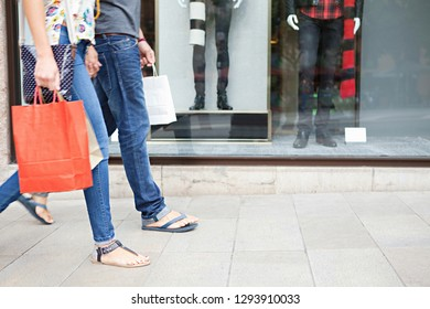 Lower section view of young couple legs walking by store window with manikins carrying shopping bags, dynamic steps, consumers in city. Travel tourists in shopping mall, leisure recreation lifestyle.