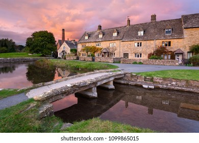 LOWER SLAUGHTER, COTSWOLDS AONB, GLOUCESTERSHIRE, ENGLAND - OCTOBER 20th 2017: Stone bridge and cotswold stone cottages by the River Eye at sunset