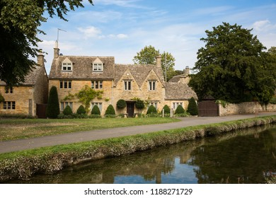 LOWER SLAUGHTER, COTSWOLDS, UK - SEPTEMBER 1, 2018. A picturesque Cotswolds stone cottage in the scenic village of Lower Slaughter with the River Windrush flowing past.