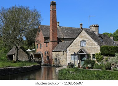 Lower Slaughter, Gloucestershire, England, UK.  14 May 2018.  The Old Mill  and water wheel on the River Eye.