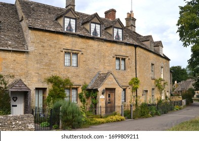 Lower Slaughter, Gloucestershire / UK - August 14, 2014: Quaint stone cottages line a street in the picturesque Cotswold village of Lower Slaughter in the UK.