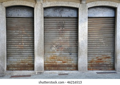 lowered rolling shutters of a disused shop, rusty, dirty and failure cityscape