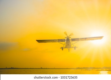 Low-flying aircraft above the lake with sun burst flare
