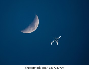 A low-flying commercial airliner passes by a crescent moon in a dark blue sky at sunset.