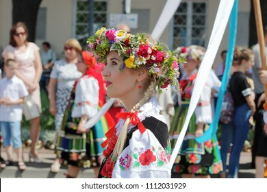 Lowicz / Poland - June 15 2017: Young girl, dressed in traditional folk regional costume, with wreath on her blond hair (upper part of body) during Corpus Christi precession, in background people