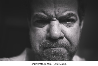 Low-key black and white monochrome portrait of a sad middle-aged man. Selective focus.