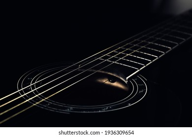 low-key photo of a fragment of a black guitar against a dark background. guitar music photo aesthetic