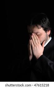 Low-key portrait of businessman praying for success
