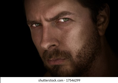 Low-key portrait of man with mysterious eyes