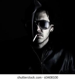 Low-key portrait of a man wearing sunglasses and smoking a cigerette.