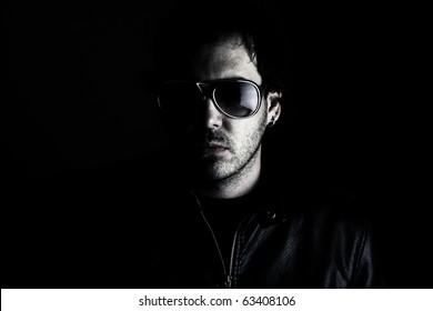 Low-key portrait of a man wearing sunglasses