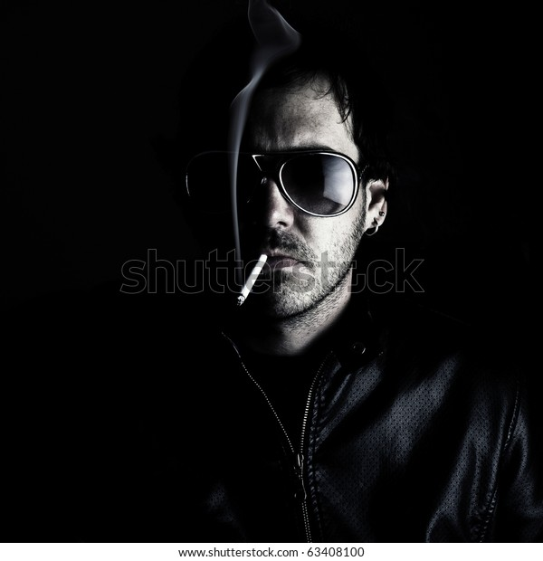 Low-key portrait of a man wearing sunglasses and smoking a cigerette.