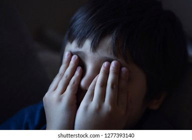 Lowkey shot of sad boy crying and rubbing eyes with his hands, Lonely child covering his face siting on sofa, Stressed child. Domestic Family violence and aggression concept violence.