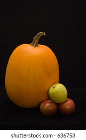 a low-key still life of a pumpkin, two red empire apples, and a golden delicious apple.