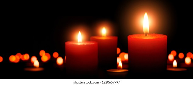 Low-key studio shot of elegant advent candles with three flames in the foreground, black background with defocused flames
