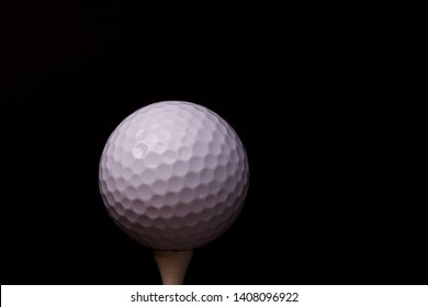 A low-key view of a Titleist golf ball on a golf tee.