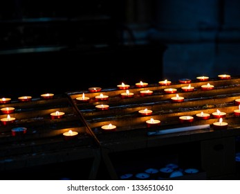 Low-light photograph of a lit candle in a Catholic church