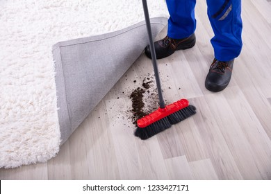 Lowsection View Of A Janitor Cleaning Dirt Under The Carpet With Mop