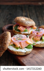 Lox - Everything bagel with smoked salmon, spinach, red onions, avocado and cream cheese over a rustic wood table background. Selective focus with blurred background.