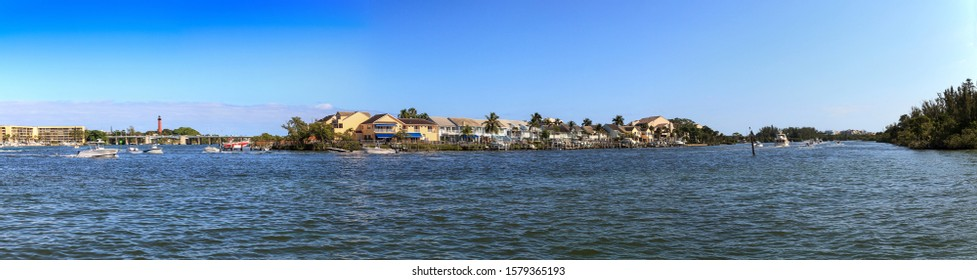 Loxahatchee River with the Jupiter Inlet Lighthouse in the background along with boats in Jupiter, Florida.