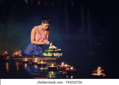 Loy Krathong Traditional Festival, Thai woman dress traditional sitting hold kratong and light the candle in Thailand.