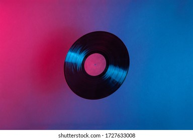 LP vinyl record lit with blue and red colorful neon light. Room for text. Vintage music futuristic concept.