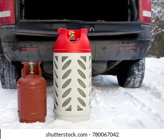 LPG gas bottles on the snow in front of the open car boot, winter scene