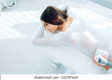 LPG massage procedure for cellulite and fat reduction. Cropped woman in white body suit getting Anti Cellulite massage on problem areas of the body, cellulite treatment,