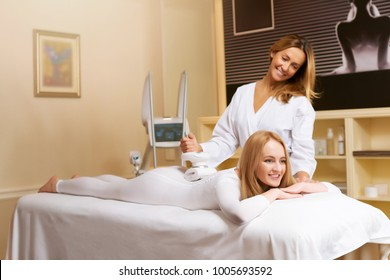 Lpg massage procedure. Smiling female and therapist beautician in salon.