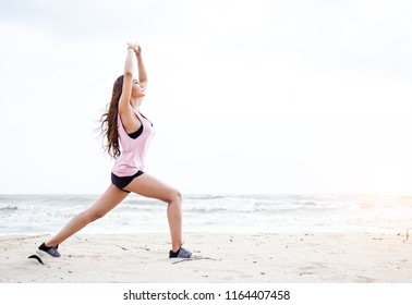 lThe beauty lady is exercise by raise her hands up in the air for stretch the muscles,on the beach,blurry light around.