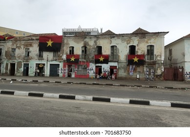 LUANDA, ANGOLA - AUGUST 23, 2017: Residents sit outside on election day in Angola underneath of the flags of the ruling People's Movement for the Liberation of Angola (MPLA) party.