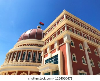 LUANDA, ANGOLA - MARCH 29 2018: National flag flies over impressive architecture of Angolan Parliament building and flag in capital city of Luanda against blue sky