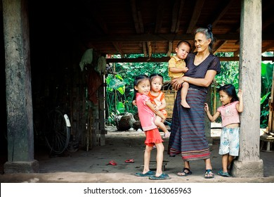 Luang Namta / Laos - JUL 06 2011: lao family with mother and cute kids waiting under their stilt house