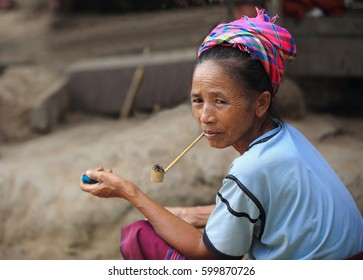 Luang Namtha prov., Laos-October 6, 2015: The Akha hill tribe are an ethnic minority living in the mountains between E.Myanmar-N.Thailand-W.Laos-S.China. Pipe-smoking old woman with modern sunglasses.