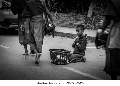 Luang Prabang. February 6, 2016. A child sits and quietly asks for handouts from monks as they passby during morning in Luang Prabang