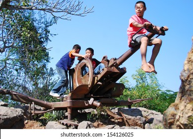 LUANG PRABANG - JAN 05:Unidentified children play on a disused anti aircraft gun on Jan 05, 2008 in Luang Prabang, Laos. The City is a UNESCO World Heritage Site and has a population of around 50,000.