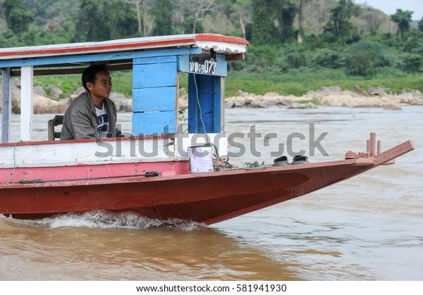 Luang Prabang , Laos -  13 January 2012: man cruising on a boat in river Mekong near Luang Prabang, Laos