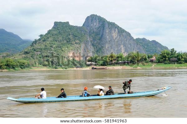Luang Prabang , Laos -  13 January 2012: people cruising on a boat in river Mekong near Luang Prabang, Laos